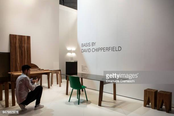 A man takes a picture of a table designed by David Chipperfield during the Salone Internazionale del Mobile at Fiera di Rho on April 17 2018 in Milan...