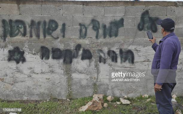 A man takes a picture of an antiArab slogan reading in Hebrew there will be a war over Judea and Samaria in the occupied West Bank village of Yasuf...