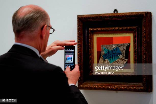 A man takes a picture of Four Fish by Spanish artist Pablo Picasso during the presentation of the exhibition Picasso's Kitchen at the Picasso Museum...