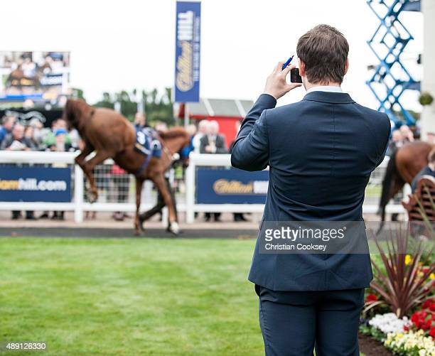 A man takes a picture of Glory Awaits as it's bucks in the parade ring before the William Hill Ayr Gold Cup on September 19 2015 in Ayr Scotland