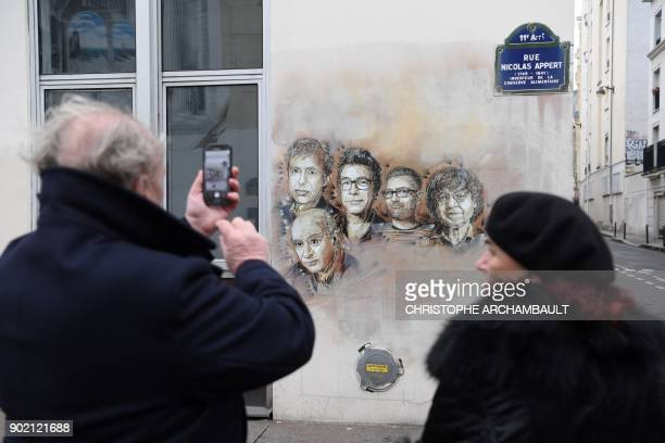 TOPSHOT A man takes a picture of portraits of late French satirical weekly Charlie Hebdo's deputy chief editor Bernard Maris French cartoonists...