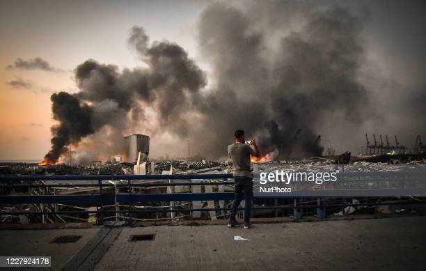 Man takes a picture of smoke rises from the port after the explosion on August 4, 2020 in Beirut, Lebanon. According to the Lebanese Red Cross, at...