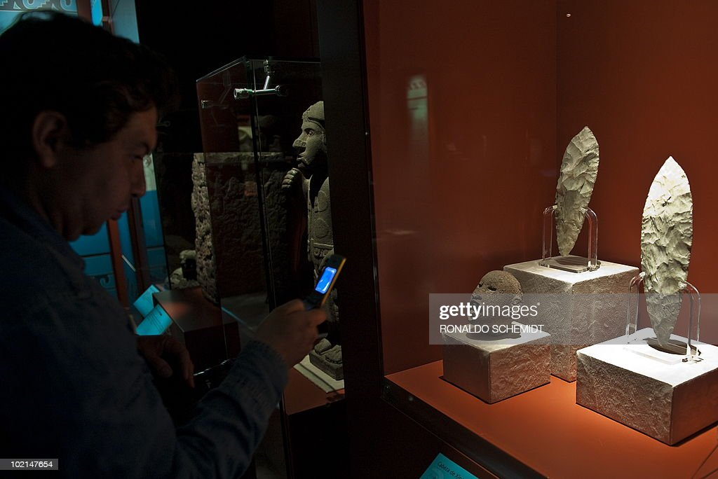 A man takes a picture of stone knives during a presentation for the press of the exhibition 'Moctezuma II' at the Templo Mayor museum, in Mexico City, on June 16, 2010. AFP PHOTO/Ronaldo Schemidt