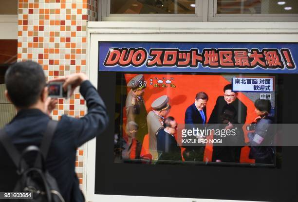 A man takes a picture of television footage of South Korean President Moon Jaein meeting North Korean leader Kim Jong Un in Tokyo on April 27 2018...