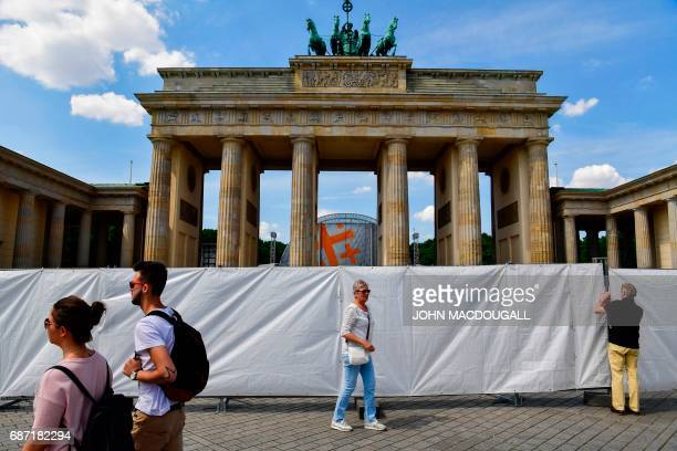 A man takes a picture of the Brandenburg Gate sealed off ahead of the Kirchentag festival celebrating the 500th anniversary of the Reformation in...
