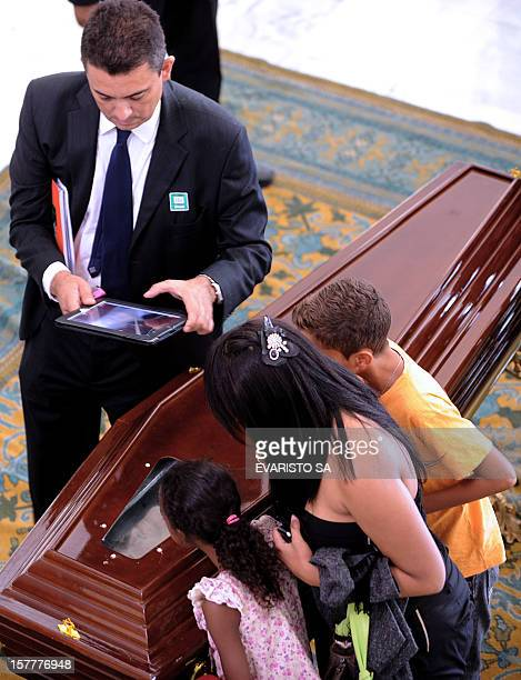 A man takes a picture of the coffin of Brazilian architect Oscar Niemeyer during his funeral at Planalto Palace in Brasilia on December 6 2012...