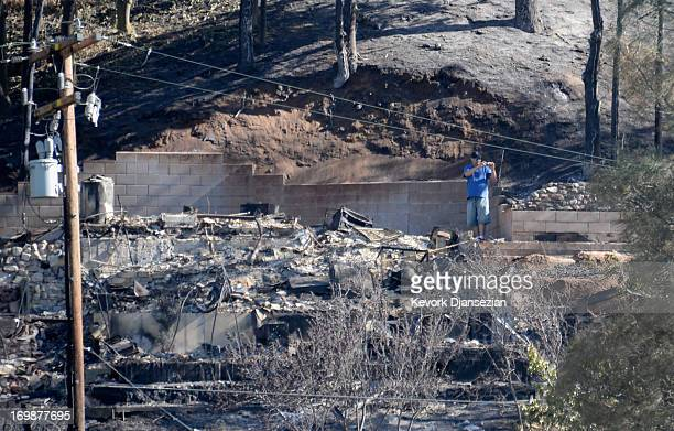 A man takes a picture of the damage near a house destroyed by fire on Lake Hughes on June 3 2013 in Palmdale California Nearly 2200 firefighters have...