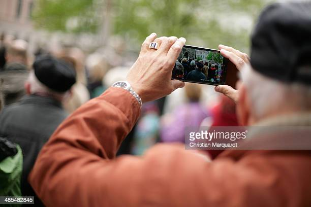A man takes a picture of the ecumenical Good Friday procession on April 18 2014 in Berlin Germany Under the theme of 'Reformation and Politics' the...