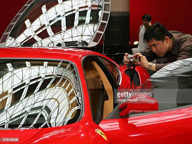 A man takes a picture of the Ferrari F430 during a news conference marking the Chinese debut of the exotic car April 19 2005 in Shanghai China The...