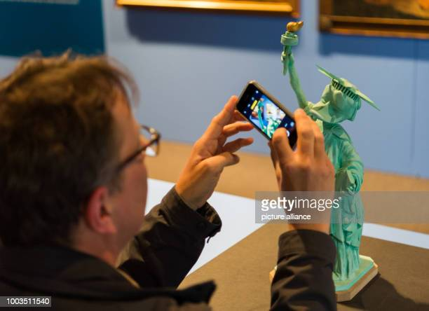 A man takes a picture of the first statue of liberty as a duck at the special exhibition 'DUCKOMENTA' in the Archäologisches Museum Hamburg Germany...