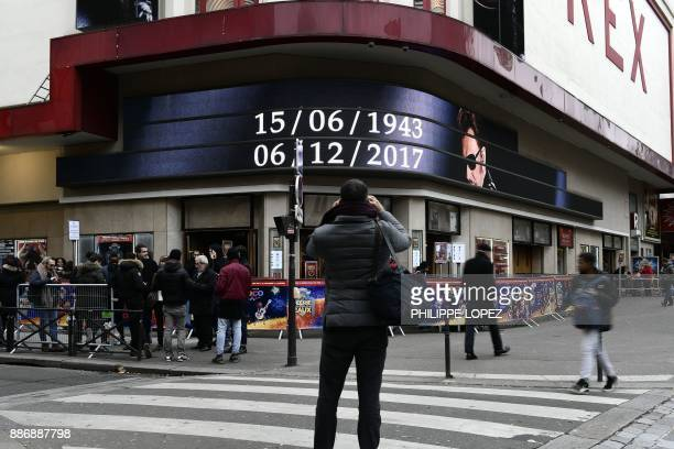 A man takes a picture of the Grand Rex cinema bearing on its facade and the date of birth and death of late French singer and actor Johnny Hallyday...