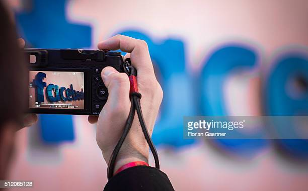A man takes a picture of the lettering of Facebook on February 24 2016 in Berlin Germany Facebook presented its Innovation Hub where new technology...