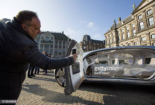A man takes a picture of the Mercedes Benz F 015 selfdriving model on March 13 2016 at the Dam square in Amsterdam This model is presented for the...