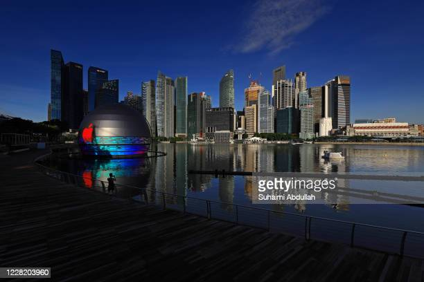 Man takes a picture of the new Apple flagship store against the city skyline at Marina Bay Sands waterfront on August 26, 2020 in Singapore. The...