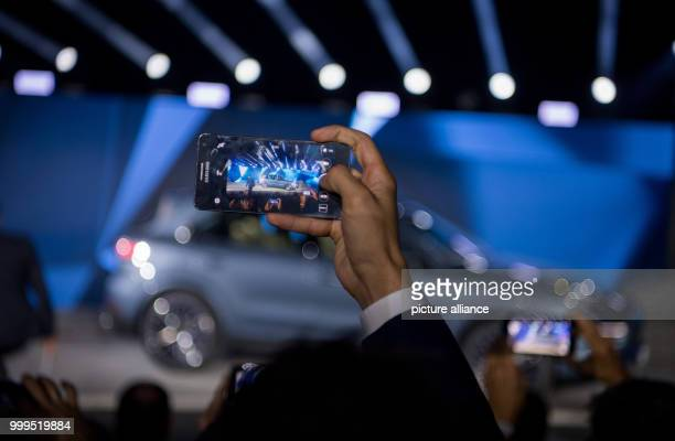 A man takes a picture of the new Porsche Cayenne that is standing on the stage during the presentation of the new series in Stuttgart Germany 29...