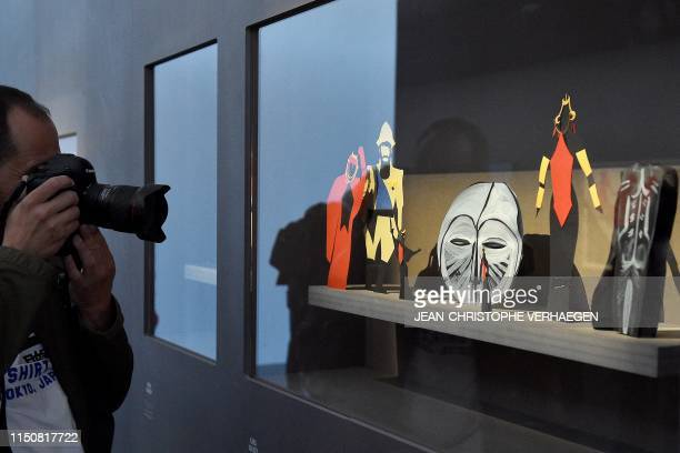 A man takes a picture of the preparatory models designed by US artist Kara Walker and displayed at the PompidouMetz museum on June 19 2019 in Metz...