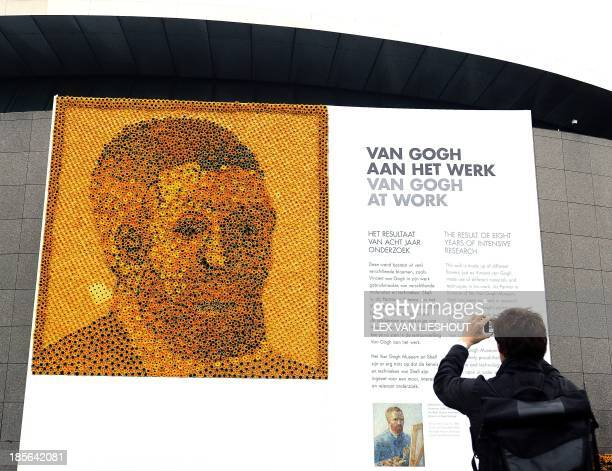 A man takes a picture of the reproduction of a selfportrait of Vincent van Gogh made with thousands of sunflowers and gerberas at the Museumplein in...