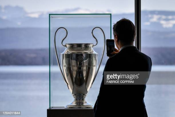A man takes a picture of the UEFA Champions League trophy displayed at the UEFA headquarters on February 28 2020 in Nyon