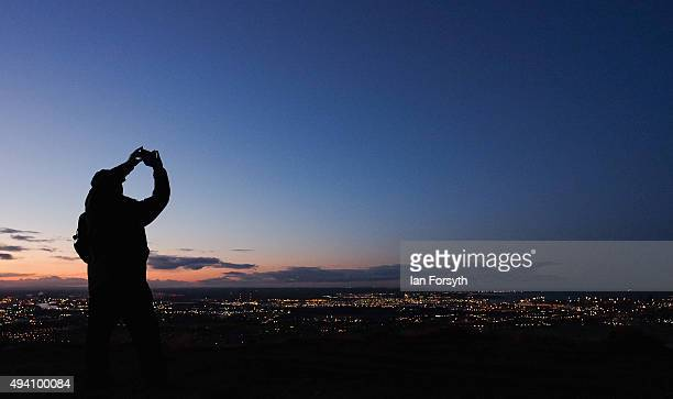 A man takes a picture overlooking Teesside during a torchlit procession on the top of the Eston Hills on October 24 2015 in Eston Cleveland The event...