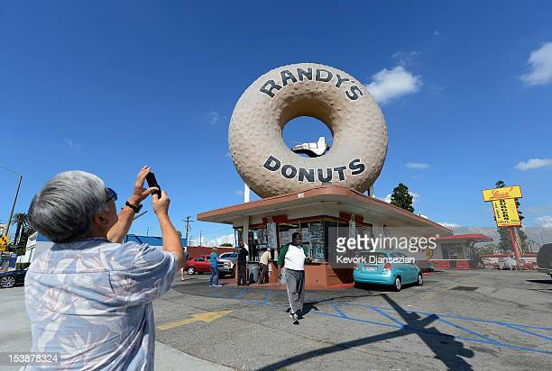 Man takes a picture with his mobile phone of a toy space shuttle placed in the dounut hole of Randy's Donuts in preparation of the ground transport...