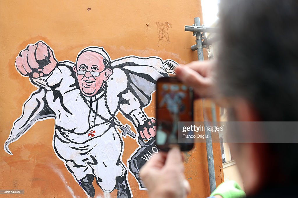 A man takes a picture with his smartphone of a graffiti featuring a 'superhero' version of Pope Francis appears in Borgo Pio, next to St. Peter's Square on January 29, 2014 in Rome, Italy. The image started circulating from the twitter account of the Vatican and has rapidly spread around the world.