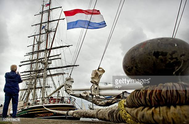 Man takes a pictures of sailboats arriving in the Dutch IJmuiden harbour after taking part in the North Sea Tall Ships Regatta race on August 17,...