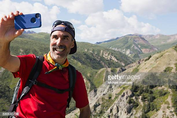 A man takes a self portrait with his cell phone camera in the mountains; Haines Junction, Yukon, Canada