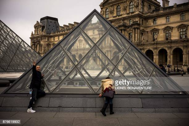A man takes a selfie as a woman looks inside the Louvre museum through a pyramid by Chinese artist Ieoh Ming Pei on november 20 2017 in Paris / AFP...