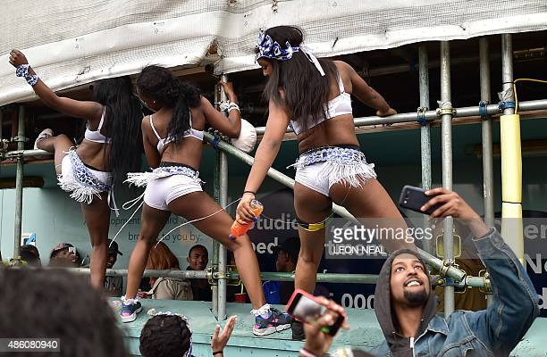 A man takes a 'selfie' as revellers dance in the streets on the second day of the Notting Hill Carnival in west London on August 31 2015 Nearly one...