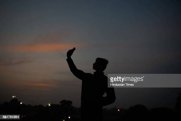 A man takes a selfie at dusk on a cold and smoggy day at Raj Ghat on December 3 2017 in New Delhi India Delhi witnessed a sharp drop in temperature...