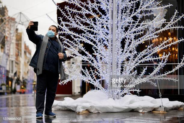 Man takes a selfie by an illuminated Christmas tree in central London on November 20 as life under a second lockdown continues in England. - The...