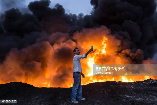 TOPSHOT A man takes a selfie in front of a fire from oil that has been set ablaze in the Qayyarah area some 60 kilometres south of Mosul on October...