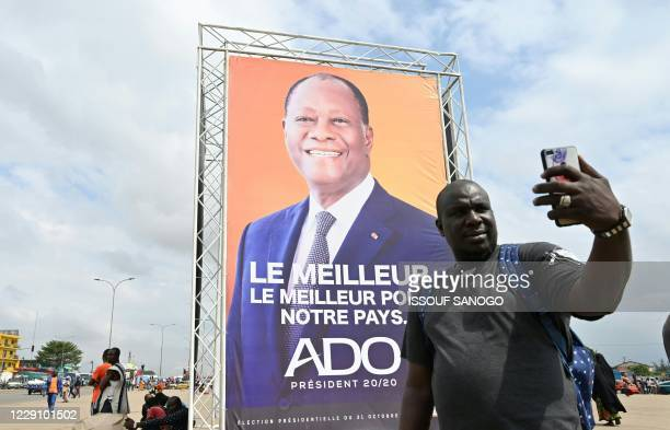 A man takes a selfie next to Ivorian President Alassane Ouattara's campaign poster in Abobo a suburb of Abidjan on October 16 ahead of the country's...