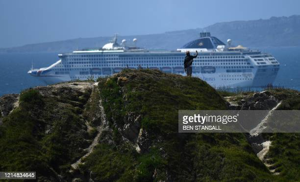 Man takes a selfie photo atop the Durdle Door rock, as a Cruise ship is seen in the sea beyond, near West Lulworth on the south coast of England on...
