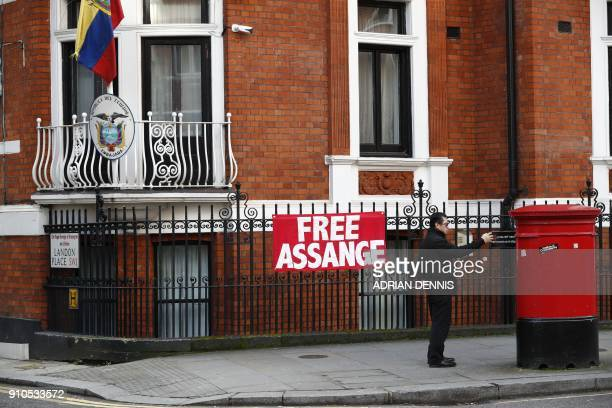A man takes a selfie photograph in front of a sign that reads 'free assange' on the facade of the Ecuadorian Embassy in London on January 26 2018...