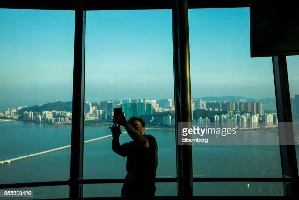 A man takes a selfie photograph using a smartphone at the observation deck of the Macau Tower in Macau China on Wednesday Sept 27 2017 Junkets flush...