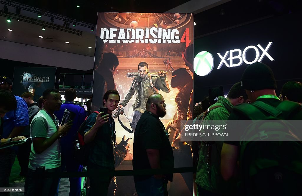 A man takes a selfie while waiting in line to play
