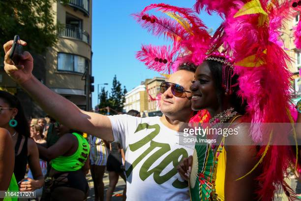 A man takes a selfie with a dancer during the 2019 Notting Hill Carnival Europe's largest street party and a celebration of Caribbean traditions and...