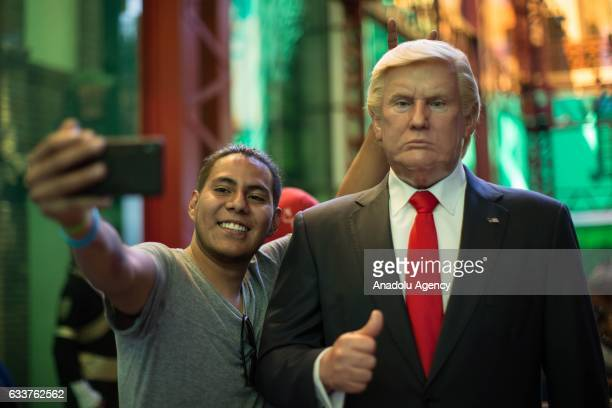 A man takes a selfie with a wax sculpture of US President Donald Trump at the Wax Museum in Mexico City Mexico on February 03 2017 The sculptures...