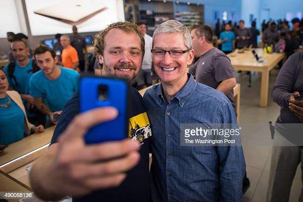 A man takes a selfie with Apple CEO Tim Cook as he talks and takes photos with employees and customers on a surprise visit to the Georgetown Apple...