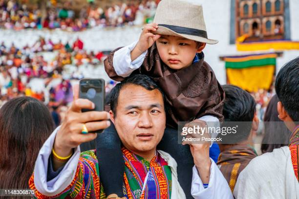 a man takes a selfie with his son on his shoulders at the paro festival - bhutan stock pictures, royalty-free photos & images