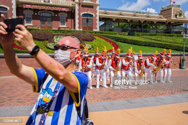 A man takes a selfie with members of a marching band at the official reopening ceremony at Walt Disney Co's Disneyland Resort on June 18 2020 in Hong...