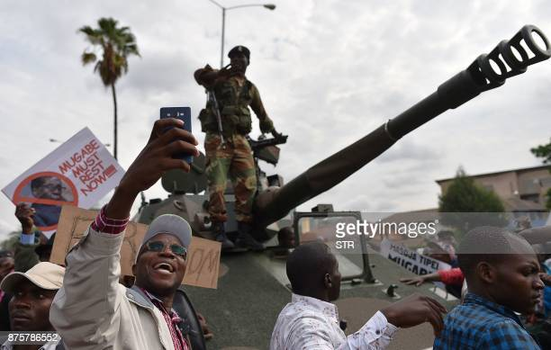 A man takes a selfiepicture of a Zimbabwean Defence Force soldier standing on a tank during a march in the streets of Harare on November 18 2017 to...