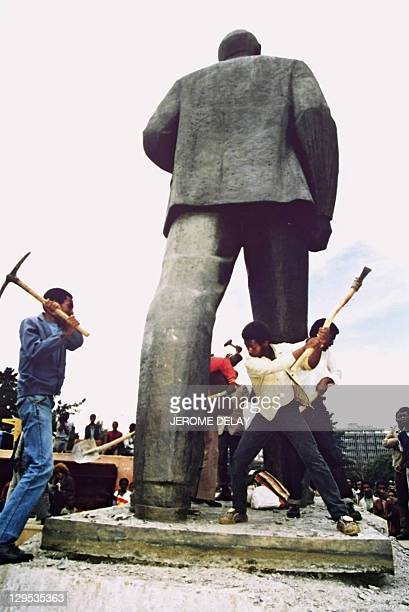 A man takes a shot at toppling the statue of Russian Bolshevik revolutionary leader Vladimir Ilyich Lenin as workers begin dismantling 23 May 1991 in...