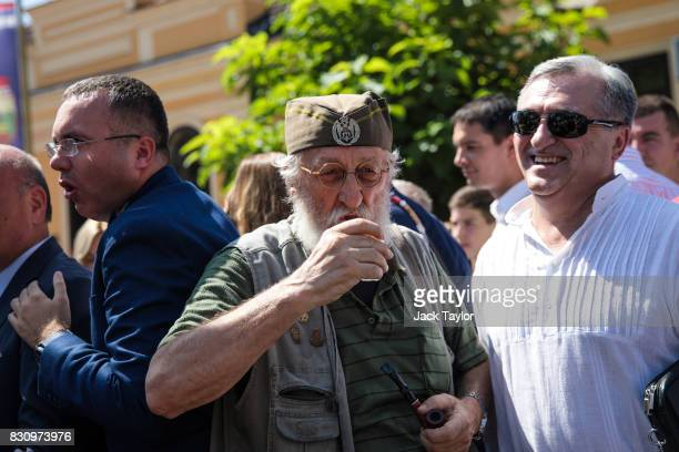 A man takes a sip of Rakia as people gather in the town centre during the Guca Trumpet Festival on August 10 2017 in Guca Serbia Thousands of...