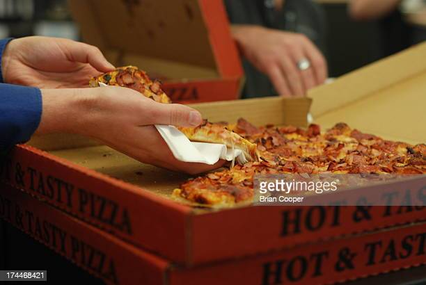 Man takes a slice of hot and tasty pizza out of a box.