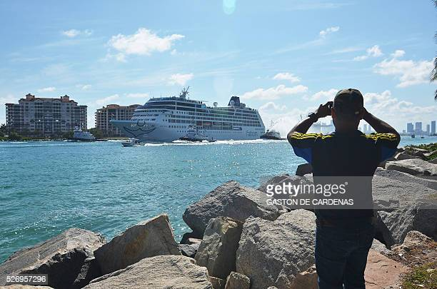 TOPSHOT Man takes a smartphone photo of the Fathom cruise ship Adonia as she departs Miami Beach Florida on her inaugural sevenday voyage to Cuba on...