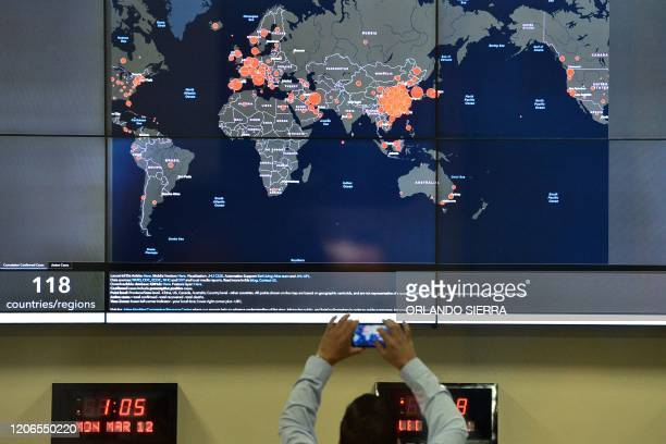 A man takes a snapshot of a map showing the countries where the COVID19 has been confirmed after Honduran President Juan Orlando Hernandez confirmed...
