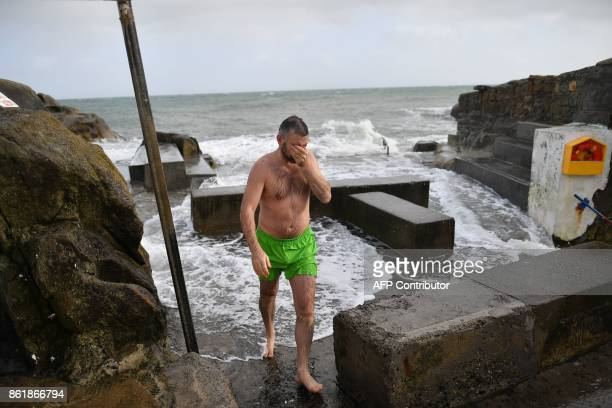 A man takes a swim at the 40 Foot swimming area on the Irish Sea coast at Glenageary County Dublin on October 16 2017 as Ireland braces for the...