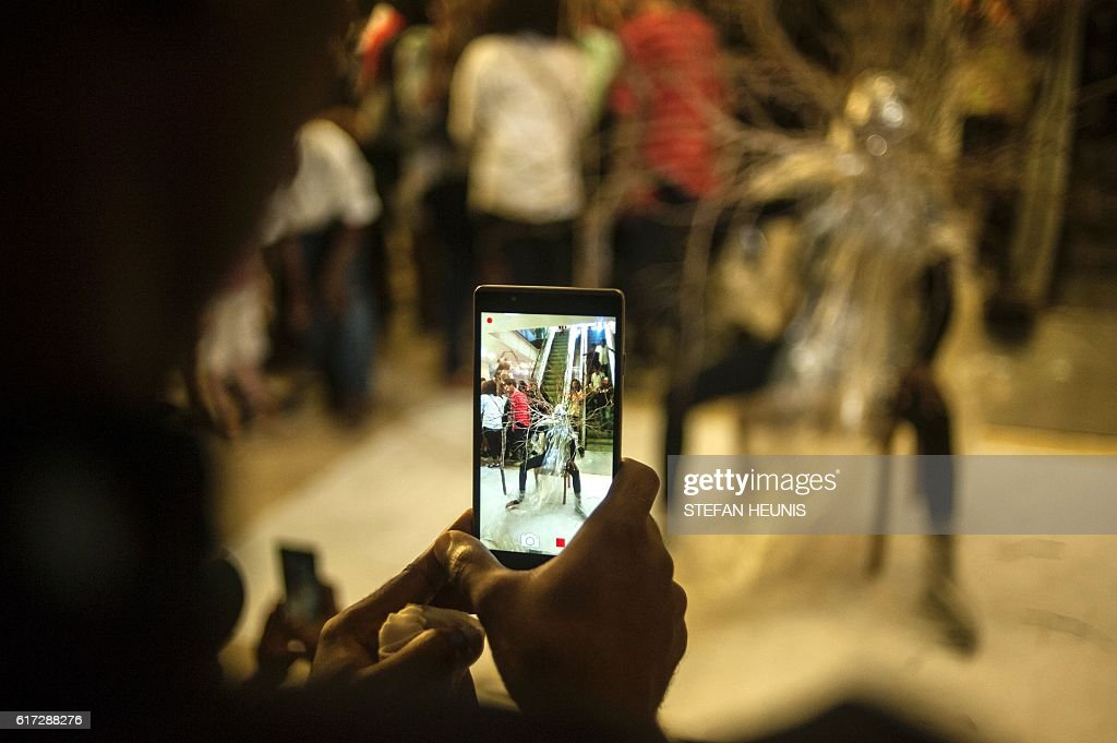 A man takes a video of performance artist Jelili Atiku during the opening of the Lagos Photo festival in Lagos on October 22, 2016. Lagos Photo was launched in 2010 and is the first and only international arts festival of photography in Nigeria. / AFP / STEFAN